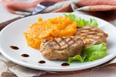 Pork steak fried on grill with mashed sweet potatoes, tasty — Stock Photo