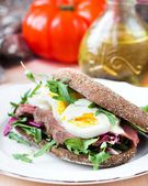 Sandwich with grilled beef steak, eggs, arugula, rye bread — Stock Photo