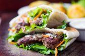 Minced meat kebab, beef balls in flat cake with vegetable — Zdjęcie stockowe