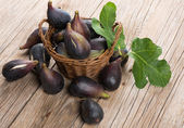 Ripe sweet figs with leaves in a basket — Stock Photo