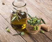 olive oil and freshly harvested olives in mortar — Stock Photo