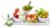 Mozzarella cheese with tomatoes,  olives and spices — Stock Photo