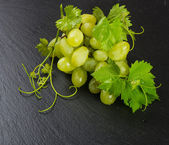 Green grape cluster on a slate  surface — Stock Photo