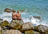 Boy and girl sitting near the sea — Stock Photo