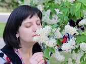 A woman sniffs a flower on a branch bird-cherry — Stock Photo