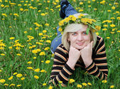 The woman lies on the grass with a wreath of flowers on her head — Stock Photo