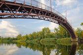 Arcuate footbridge over the River — Stock Photo