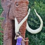 Постер, плакат: A girl stands near a mammoth layout