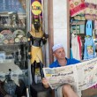 Egypt. Europempretends to read Egyptinewspaper while sitting on site of merchant stalls. — Stock Photo #34390111