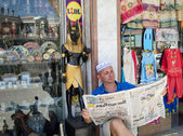 Egypt. European man pretends to read Egyptian newspaper while sitting on the site of the merchant stalls. — Stock Photo