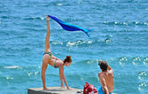 Beautiful woman near the sea front of a man doing the splits — Stock Photo