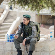 Stock Photo: Israeli police min uniform sitting on parapet in Jerusalem
