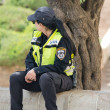 Stock Photo: Israeli womin police uniform sitting on parapet in city of Jerusalem