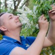 The man enthusiastically sniffing the smell of bird-cherry — Stock Photo