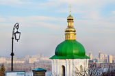 Kiev - Pechersk Lavra.Golden dome of the church on a background of the Dnieper River and buildings — Stockfoto