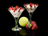 Tennis sphere and wild strawberry with cream in two glasses with — Stock Photo