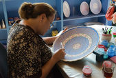 Woman painting a beautiful ceramic dish. — Stock Photo