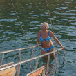 Woman that leaves the water holds handrails of yacht's gangplank - Stock Photo