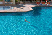 Bright blue water of swimming pool with sunlight glints and woma — Stock Photo