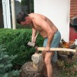 Strong man is chopping wood with an axe and hummer. Renewable re — Stockfoto