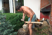 Strong man is chopping wood with an axe and hummer. Renewable re — Stock Photo