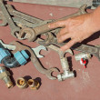 Foto Stock: Many wrenches and valves with reached out hand of plumber on lig