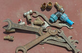 Many wrenches and valves on light brown background. — Stock Photo