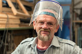 The portrait of craftsman that picked up face shield. — Stock Photo
