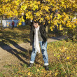 Womis standing under autumn tree in bright sunlight. — Stock Photo #36593457