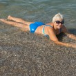 Aged lady is lying on water's edge at the sea beach. — Stock Photo #42237561