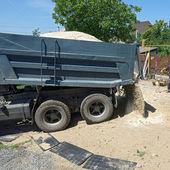 Tips lastbil dumpning sand i trädgården. — Stockfoto