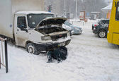 The driver of the car repairs lying in the snow — Stock Photo