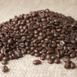Bulk coffee beans on sacking — Stock Photo