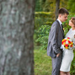 Young bride and groom standing in a park — Stock Photo #15805035