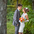 Young bride and groom standing in a park — Stock Photo