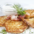 On a plate lined with fried potato pancakes with fried bacon and - Stock Photo