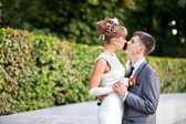 Bride and groom standing in a park — Stock Photo