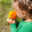 Girl  sniffing a bouquet of orange flowers — Stock Photo