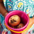 Girl holds a toy bucket with new potatoes — Stock fotografie