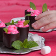 Stock Photo: Chocolate candies with pink cream and mint leaves