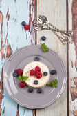 Creamy panacotta with fresh raspberries and blueberries — Stock Photo