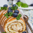 Sweet Biscuit Roll Cake with fresh berries and a cup of tea — Stock Photo