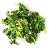 Spinach with garlic and pine nuts — Stock Photo