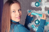 Girl decorates the Christmas tree — Stock Photo