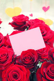 Red roses with a blank gift tag — Stock Photo