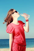 Woman drinking mineral water on the beach — Stock Photo
