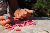 Hands lying on rose petals — Stock Photo