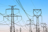 Jungle of high voltage power electricity towers under sky — Stock Photo