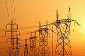 Gün batımı sırasında yüksek gerilim elektrik direkleri — Stok fotoğraf