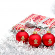 Three red christmas ball and present on white background - Stock Photo